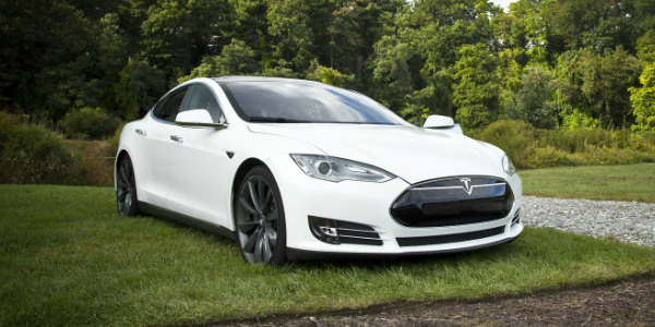 tesla car parked on the grass in front of a forest, symbolizing this article's focus on tesla repairs and its impact on car insurance